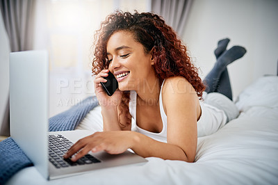 Buy stock photo Full length shot of an attractive young woman making a phonecall and using her laptop while lying on her bed at home