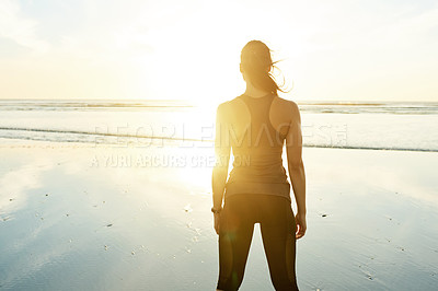 Buy stock photo Rearview shot of an attractive and athletic young woman working out on the beach