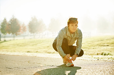 Buy stock photo Full length shot of an attractive mature sportswoman tying her laces during an early morning run in the park