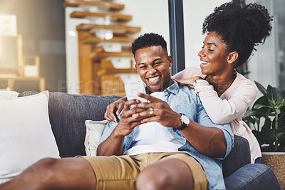 Buy stock photo Shot of a happy young couple using a mobile phone together on the sofa at home