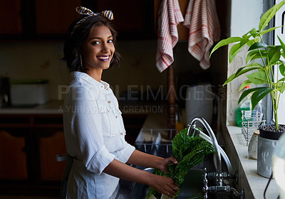 Buy stock photo Shot of a young woman rinsing spinach in a kitchen sink at home