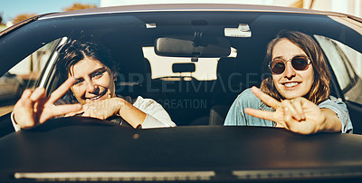 Buy stock photo Cropped portrait of two attractive young women showing peace signs while enjoying a roadtrip