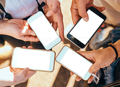 Buy stock photo High angle shot of a group of unrecognizable young friends using their cellphones while standing outside
