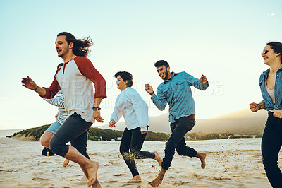 Buy stock photo Cropped shot of a group of young friends running out on the beach