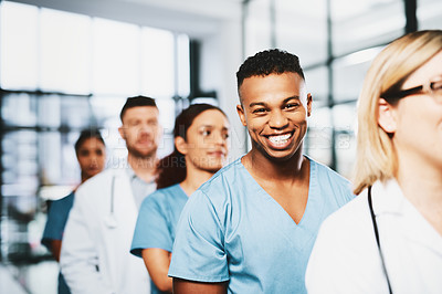 Buy stock photo Portrait of a young medical practitioner standing in a line amongst his colleagues in a hospital
