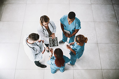 Buy stock photo High angle shot of a group of medical practitioners analyzing x-ray scans on a digital tablet in a hospital