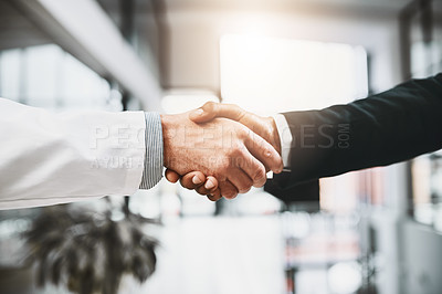 Buy stock photo Closeup shot of a doctor shaking hands with a businessman