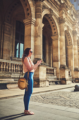 Buy stock photo Full length shot of an attractive young woman sending text messages while exploring the city of Paris in France