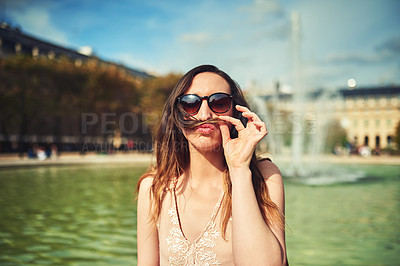 Buy stock photo Cropped portrait of an attractive young woman making a moustache with her hair while  exploring the city of Paris in France