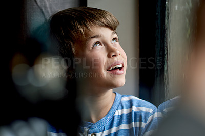 Buy stock photo Shot of a little boy sitting by the window while watching the rain