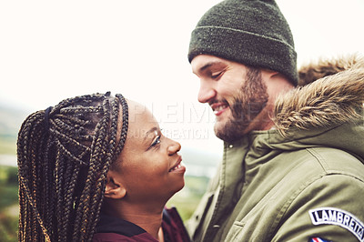 Buy stock photo Cropped shot of a young couple being affectionate outdoors