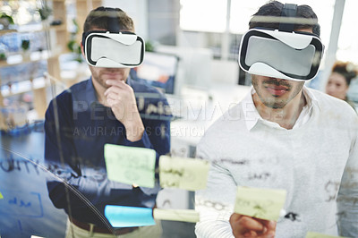 Buy stock photo Shot of two businessmen wearing VR headsets while brainstorming together in an office