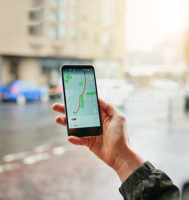 Buy stock photo Closeup shot of an unrecognizable woman using a cellphone to find directions in the city on a rainy day