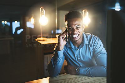 Buy stock photo Cropped portrait of a handsome young businessman making a phonecall while working late at night in a modern office