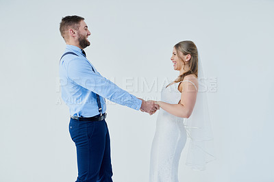 Buy stock photo Studio shot of a happy young couple holding hands on their wedding day against a gray background