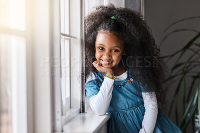 Buy stock photo Portrait of an adorable little girl standing by the window at home