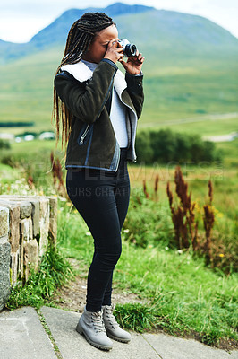 Buy stock photo Shot of a young woman taking pictures with her camera while out exploring nature
