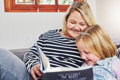 Buy stock photo Shot of a little girl reading a book with her mother at home