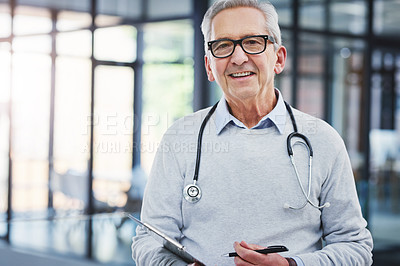 Buy stock photo Cropped portrait of a handsome mature male doctor standing with his clipboard in the hospital