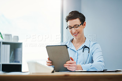 Buy stock photo Cropped shot of an attractive young female doctor using her tablet while sitting at her desk in the hospital