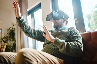 Buy stock photo Cropped shot of a young man using a virtual reality headset on the sofa at home