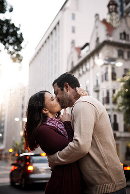 Buy stock photo Shot of a happy young couple sharing a romantic moment in the city