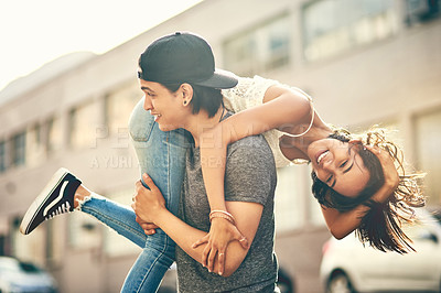 Buy stock photo Shot of a handsome young man throwing his girlfriend over his shoulder