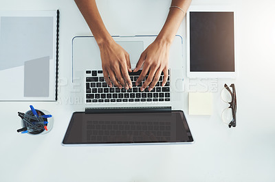 Buy stock photo High angle shot of an unrecognizable woman sitting at her office desk busy typing on her laptop