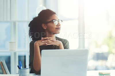 Buy stock photo Shot of a young businesswoman sitting at her office desk and looking out of the window