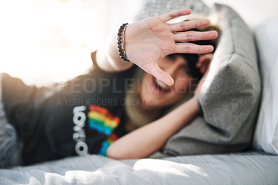 Buy stock photo Cropped portrait of an attractive young woman gesturing to stop while lying on her bed at home