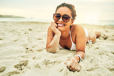 Buy stock photo full length portrait of an attractive young woman lying in the sand on the beach