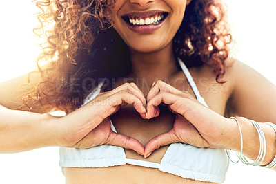 Buy stock photo Cropped shot of an unrecognizable young woman making a heart shape with her hands while standing on the beach