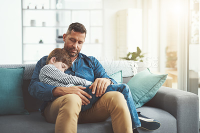Buy stock photo Shot of a tired little boy sleeping in his father's arms while being seated on a sofa at home during the day