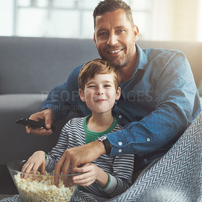 Buy stock photo Portrait of a carefree young boy and his father watching a movie together while being seated on the floor and eating popcorn at home during the day