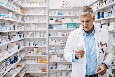 Buy stock photo Shot of a pharmacist reading the label on a product in a drugstore