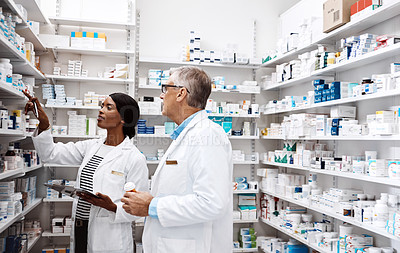 Buy stock photo Shot of two pharmacists working together in a drugstore