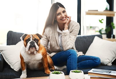 Buy stock photo Shot of an attractive young woman sitting on her sofa relaxing at home with her dog