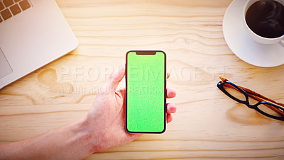 Buy stock photo High angle shot of an unrecognizable man holding a smartphone displaying chroma key on the screen in an office environment