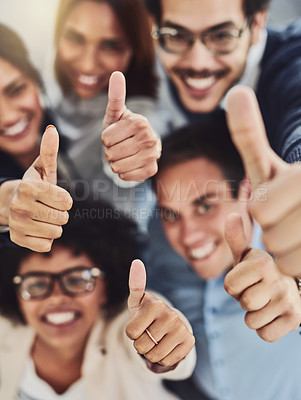 Buy stock photo Portrait of a group of cheerful businesspeople showing thumbs up in an office during the day