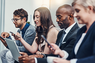 Buy stock photo Cropped shot of a group of businesspeople using various digital devices in an office