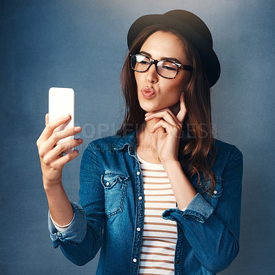 Buy stock photo Studio shot of a beautiful young woman taking a selfie against a blue background