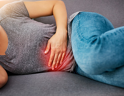 Buy stock photo Closeup of an unrecognizable woman holding her stomach in discomfort while trying to get rest on a sofa at home during the day