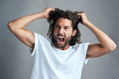Buy stock photo Studio shot of a young man screaming against a grey background