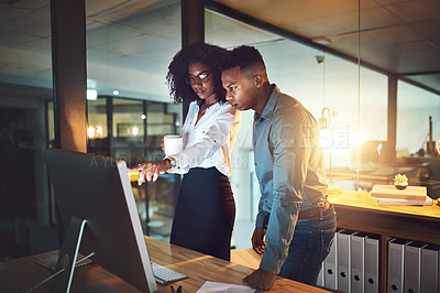 Buy stock photo Shot of two businesspeople working together on a computer in an office at night