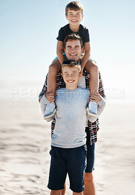 Buy stock photo Shot of a father having fun with his young sons at the beach