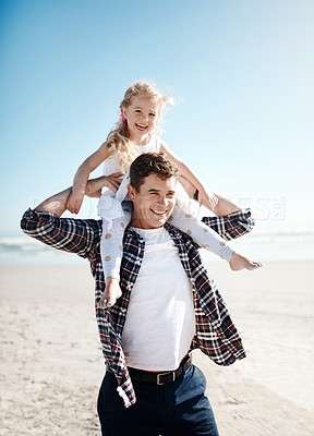 Buy stock photo Shot of a father carrying his young daughter on his shoulders on a sunny day at the beach
