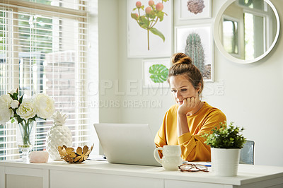 Buy stock photo Shot of a young woman using a laptop while working from home