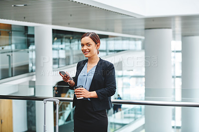 Buy stock photo Cropped portrait of an attractive young businesswoman sending a text message while standing in the airport