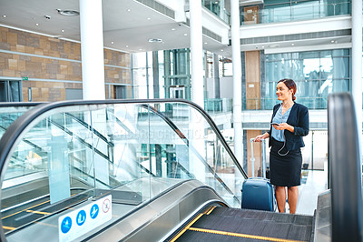 Buy stock photo Full length shot of an attractive young businesswoman making a phonecall while standing on an escalator in the airport