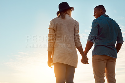 Buy stock photo Rearview shot of a happy young couple holding hands outdoors